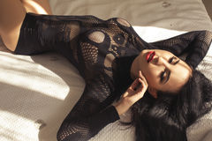 Sexy beautiful woman with dark hair in black lingerie lying on bed Royalty Free Stock Photos