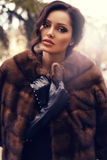 Sexy beautiful woman with dark hair in luxurious fur coat posing at park Royalty Free Stock Photos
