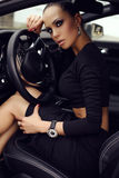 Beautiful woman with dark hair posing in luxurious auto. Fashion outdoor photo of beautiful woman with dark hair in black elegant dress posing in luxurious auto stock photos