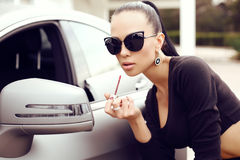 Sexy beautiful woman with dark hair posing beside luxurious auto Stock Images