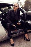 Beautiful woman with dark hair posing in luxurious auto. Fashion outdoor photo of beautiful woman with dark hair in black leather clothes posing in luxurious stock photos
