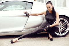 Sexy beautiful woman with dark hair posing beside luxurious auto Royalty Free Stock Photography
