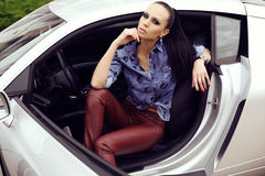 Sexy beautiful woman with dark hair posing in luxurious auto Royalty Free Stock Images