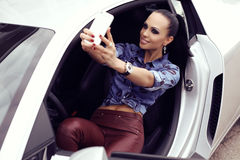 beautiful woman with dark hair posing in luxurious auto Stock Photography