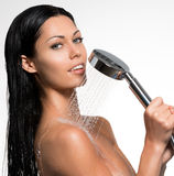Sexy beautiful woman holds shower in hands Royalty Free Stock Photo