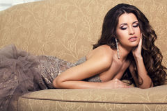 Sexy beautiful woman in luxurious dress lying on divan Stock Photos