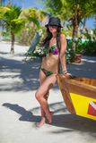 Sexy beautiful woman near a boat on exotic resort Royalty Free Stock Image