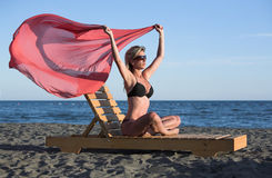 Sexy, beautiful woman with pink shawl, black bikin. Young woman sits on sunbed at the beach, wind blows her pink ribbon Royalty Free Stock Photography