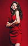 Sexy beautiful woman in red dress with curly hair Stock Images