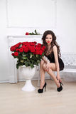 beautiful woman with red roses bouquet in interior apartmen Stock Photos