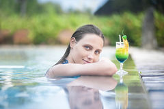 Sexy woman relaxing in the pool with a cocktail. Sexy beautiful woman relaxing in the blue pool with a green cocktail Stock Photography
