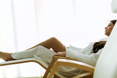 Sexy and beautiful woman relaxing in a chair dressed in a robe Stock Photo