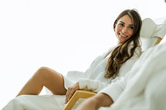 Sexy and beautiful woman relaxing in a chair dressed in a robe Royalty Free Stock Photography