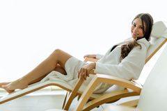 Sexy and beautiful woman relaxing in a chair dressed in a robe Stock Photos
