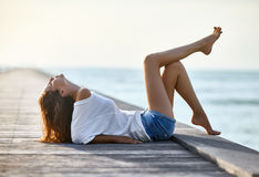 Sexy beautiful woman relaxing on pier with sea view. Vacation concept Royalty Free Stock Image
