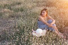 Sexy Beautiful woman sitting in flower field sadly and lonelines Royalty Free Stock Images