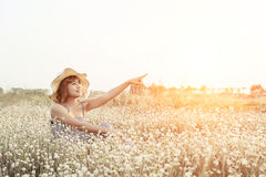 Sexy Beautiful woman wearing hat and smiley pointing her finger. Into the sky sitting in flower field  with fresh air in the morning Royalty Free Stock Image