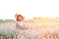 Sexy Beautiful woman wearing hat and smiley sitting in flower fi. Eld  with fresh air in the morning Stock Photography