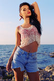 Sexy beautiful woman wears a top with jeans shorts and posing beach Royalty Free Stock Image
