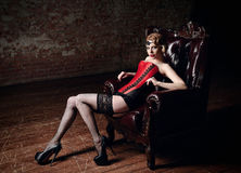 Sexy beautiful young girl dressed in corset, stockings and panties sitting in chair. Retro vintage style Royalty Free Stock Images