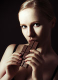 Sexy beautiful young woman eating chocolate on a dark Stock Photography