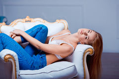 Sexy beautiful young woman posing on vintage chair. Girl in jeans and white bra. Stock Photography