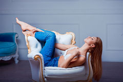 Sexy beautiful young woman posing on vintage chair. Girl in jeans and white bra. Royalty Free Stock Image