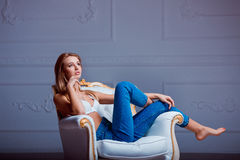 Sexy beautiful young woman posing on vintage chair. Girl in jeans and white bra. Stock Images