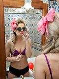 Sexy beautiful young woman wearing black panties and mauve bra looking in the mirror in bathroom. Sensual blonde with sunglasses Royalty Free Stock Photos
