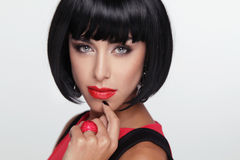 Sexy beauty brunette woman with Red Lips. Makeup. Stylish Fringe. Black Short Hair Style. Jewelry. Fashion photo Royalty Free Stock Images