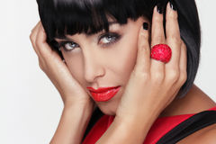 Sexy beauty brunette woman with Red Lips. Makeup. Stylish Fringe. Black Short Hair Style. Jewelry. Fashion photo Royalty Free Stock Image