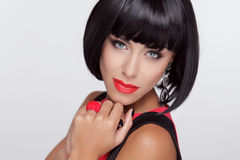 Sexy beauty brunette woman with Red Lips. Makeup. Stylish Fringe. Black Short Hair Style. Jewelry. Fashion photo Royalty Free Stock Photo