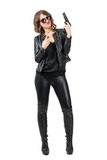 Sexy beauty wearing black leather and boots holding handgun with two finger peace hand gesture Royalty Free Stock Photography