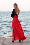 Sexy beauty woman in fluttering red dress at the coast. Fashion woman Stock Photography