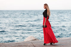 Sexy beauty woman in fluttering red dress at the coast. Fashion woman Royalty Free Stock Image