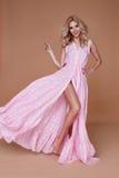 Sexy beauty woman pretty face tan skin wear baby pink silk dress Stock Image