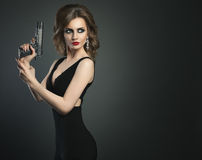Sexy beauty young woman with gun on a dark bg portrait Stock Photo