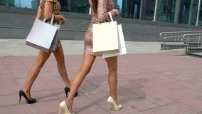 Sexy benen van mooie meisjes die met het winkelen zakken gaat close-up van vrouwelijke benen in hoge hielen Met het winkelen zakk stock footage