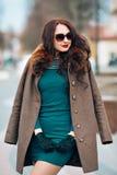 Sexy betoverend donkerbruin meisje, mooie jonge vrouw met elegant lang donker haar, die modieuze zonnebril, in groen dragen Stock Afbeeldingen