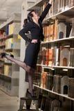 Sexy bibliothecaris die voor een boek bereikt royalty-vrije stock fotografie