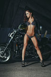 Sexy biker fitness girl with perfect slim body on black motorbike Stock Image