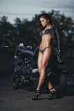 Sexy biker fitness girl with perfect slim body on black motorbike Stock Photography