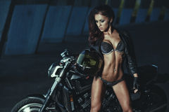 Sexy biker fitness girl with perfect slim body on black motorbike Stock Photo