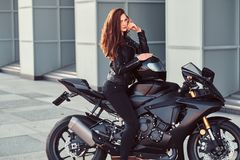 A biker girl sitting on her superbike outside a building. A biker girl wearing black leather jacket sitting on her superbike outside a building royalty free stock photos
