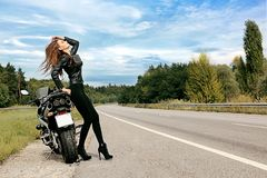 Sexy biker girl. Stands on the road near the motorcycle and touching her hair Royalty Free Stock Images