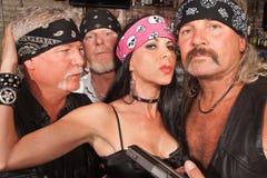 Sexy Biker Woman with Boyfriends. Sexy mature white female with three biker gang boyfriends Stock Image