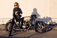 Biker girl on caferacer motorcycle. royalty free stock photography