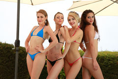 Sexy bikini girls. Four happy sexy bikini girls standing under umbrellas Stock Photography