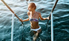 Sexy bikini smiling woman coming out of water holding onto the handrails. Young model with slim weight loss body. Swimming in summer vacation travel royalty free stock photography