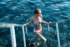 Sexy bikini smiling woman coming out of water holding onto the handrails. Young model with slim weight loss body. Swimming in summer vacation travel royalty free stock photo